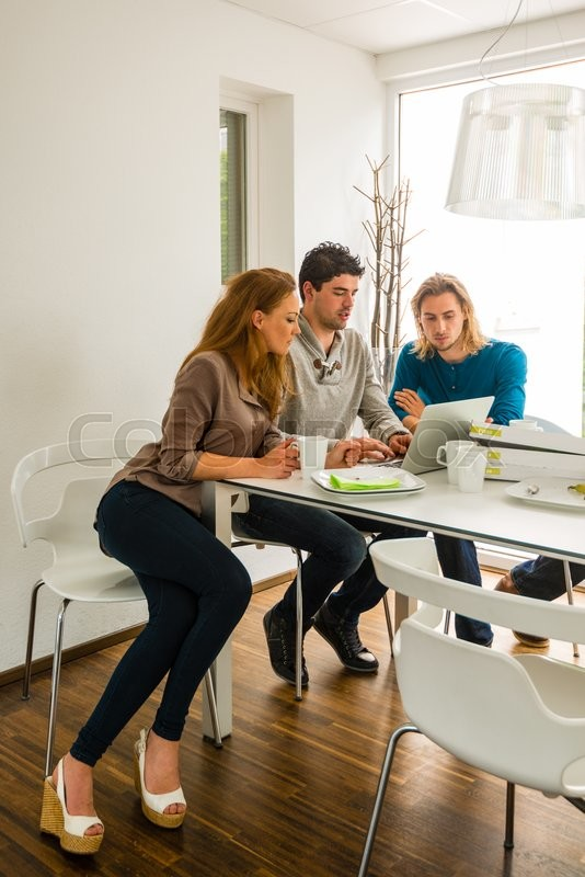 Stock image of 'Start-up business team in meeting, working on computer after having pizza in a bright room'