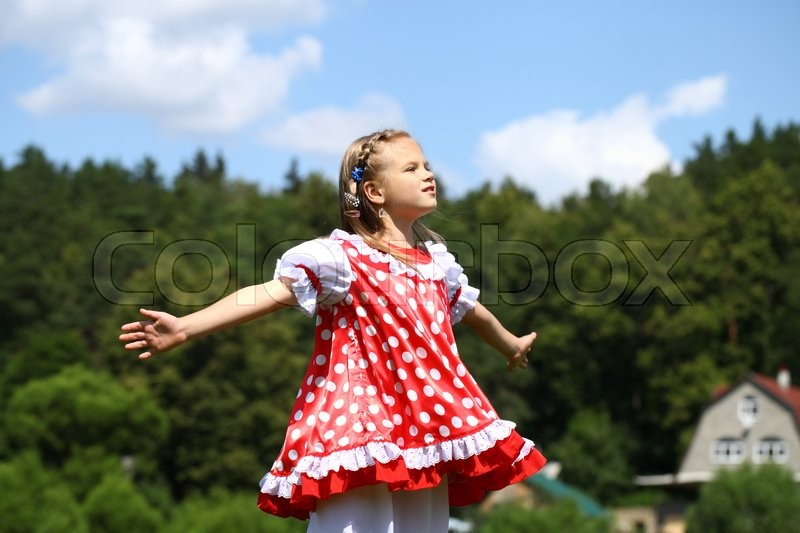 Stock image of 'Little girl in a red polka-dot sundress into a major run on green field'