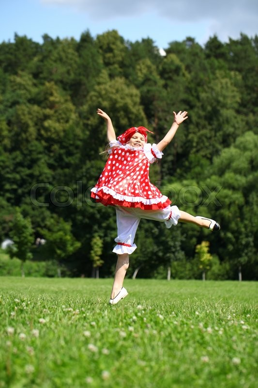 Stock image of 'Little girl in a red sundress jumping for joy on a green field'