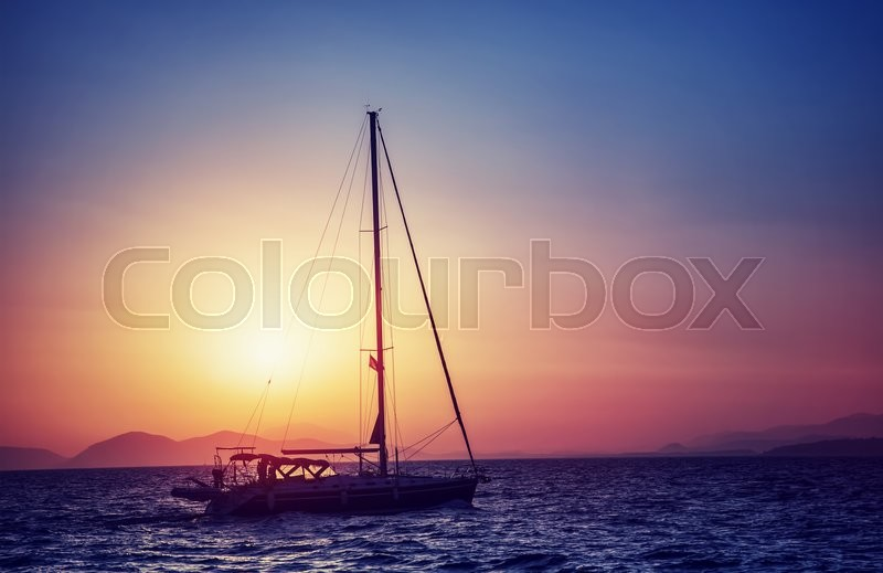 Stock image of 'Silhouette of sailboat on sunset, water transport in bright yellow sun light, sea trip in the evening, traveling around Greek islands'