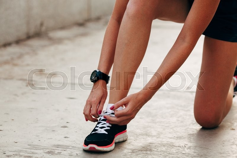 Stock image of 'body parts of runner woman tying laces at sunset'