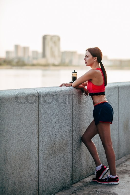 Stock image of 'Female runner with bottled water tired from running standing near granite parapet, looking far away'