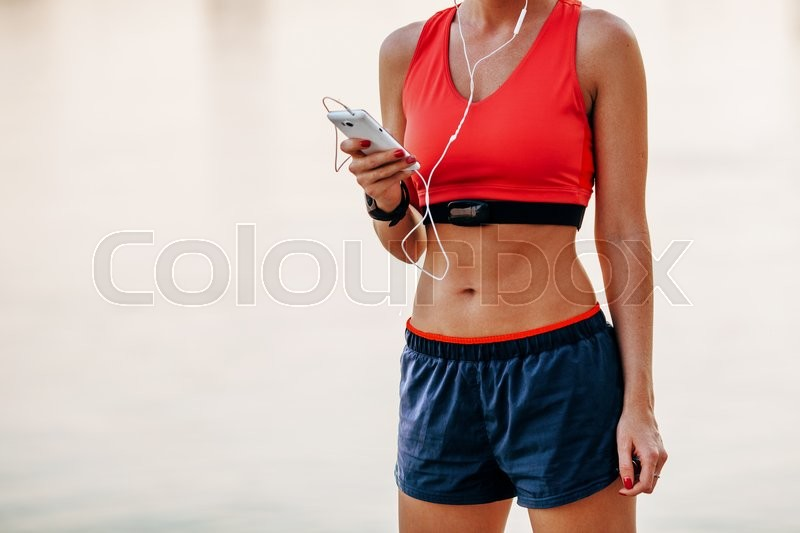 Stock image of 'Image of young woman taking a break form workout using mobile phone outdoors.'