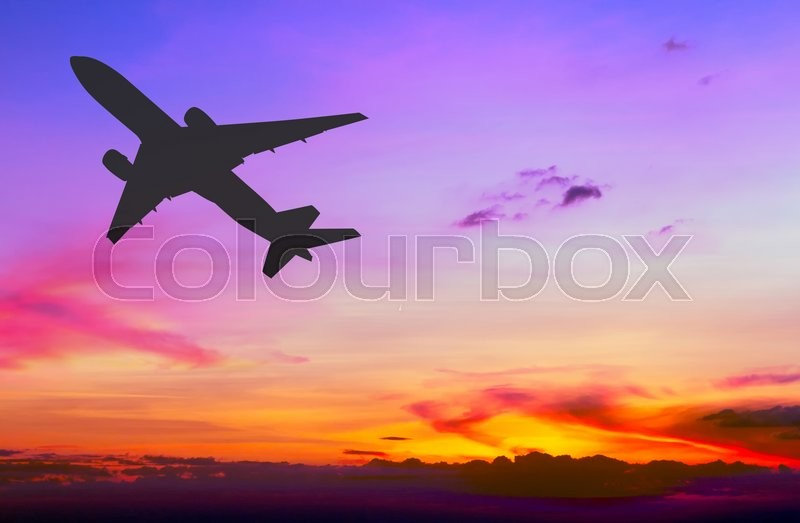 Stock image of 'Silhouetted commercial airplane flying at sunset'