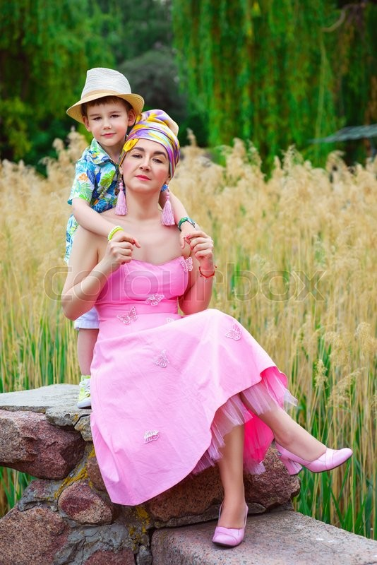 Stock image of 'Loving son hugging his stylish mother in park. '