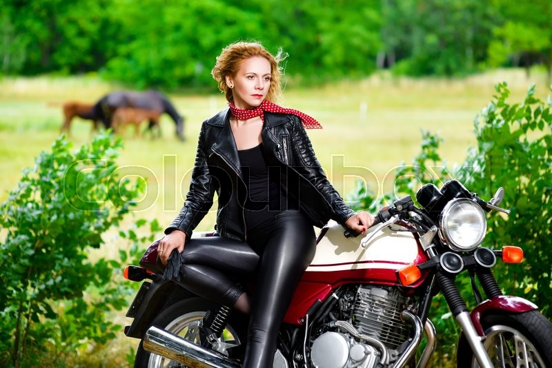 Stock image of 'Biker girl in a leather jacket on a motorcycle against the background of horses.'