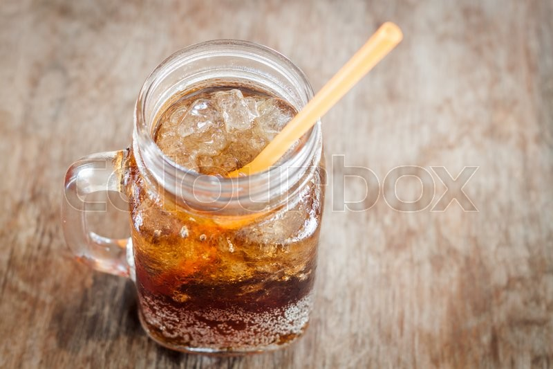 Stock image of 'Glass of cola with ice on wooden table, stock photo'
