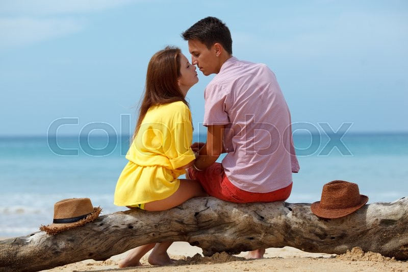 Stock image of 'lovely couple sitting on a log at the beach'