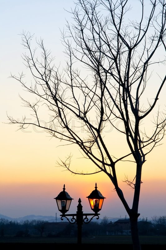 Stock image of 'Street lamp at sunset with sun on background'