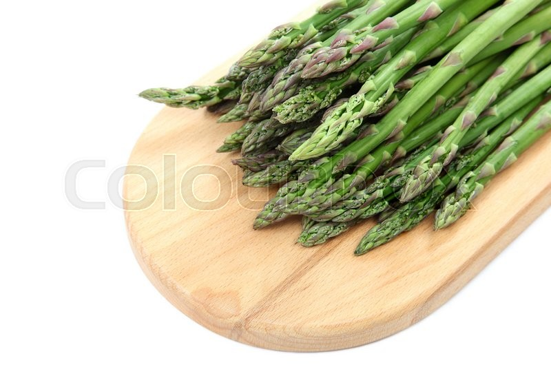 Stock image of 'Fresh green asparagus on a wooden cutting board isolated on white background.'