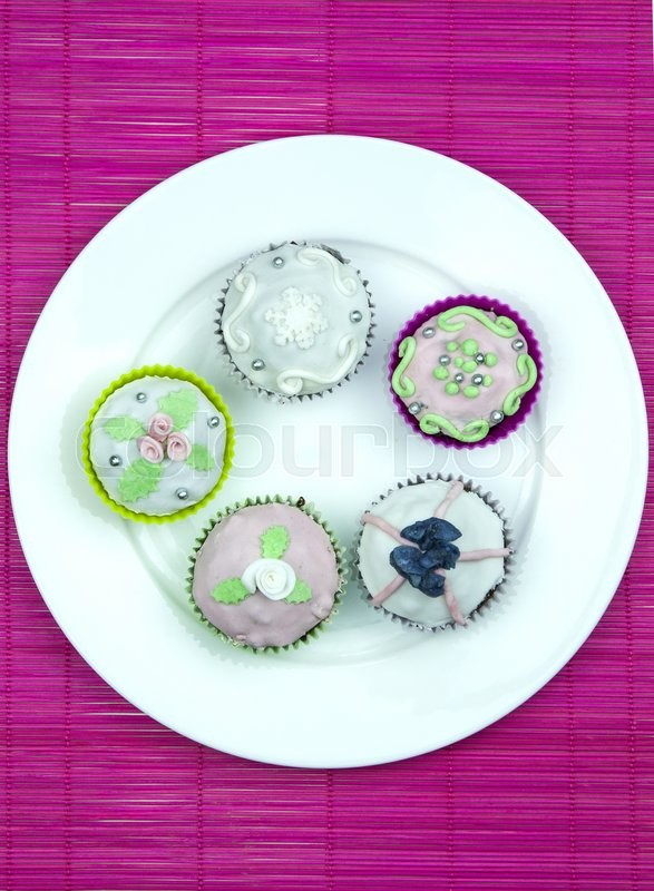 Stock image of 'Five decorated muffins  on a wooden and pink placemat.'