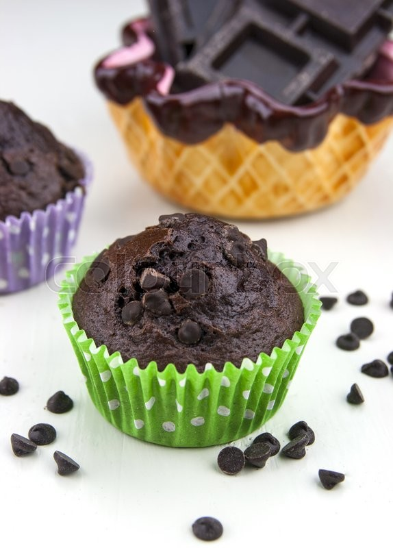 Stock image of 'Close up of chocolate muffins on a white table with a lot of chocolate's drops'