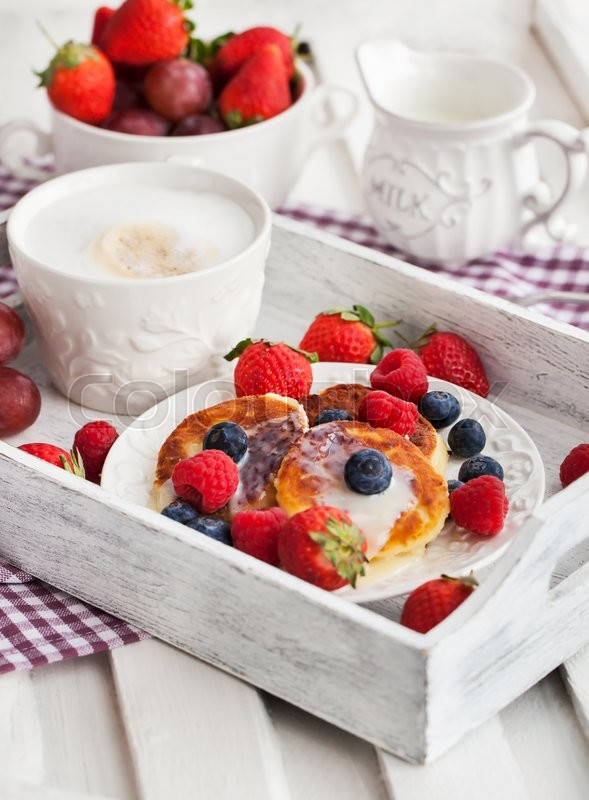 Stock image of 'Cheese pancakes (syrniki) with fresh strawberry, raspberry,  blueberry and coffee on the tray'