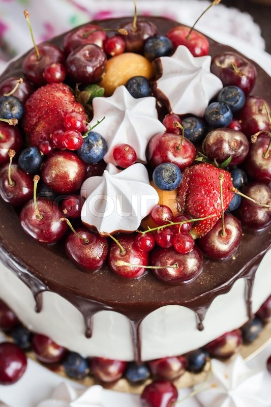 Stock image of 'Delicious homemade cake decorated with chocolate, meringues and fresh berries'