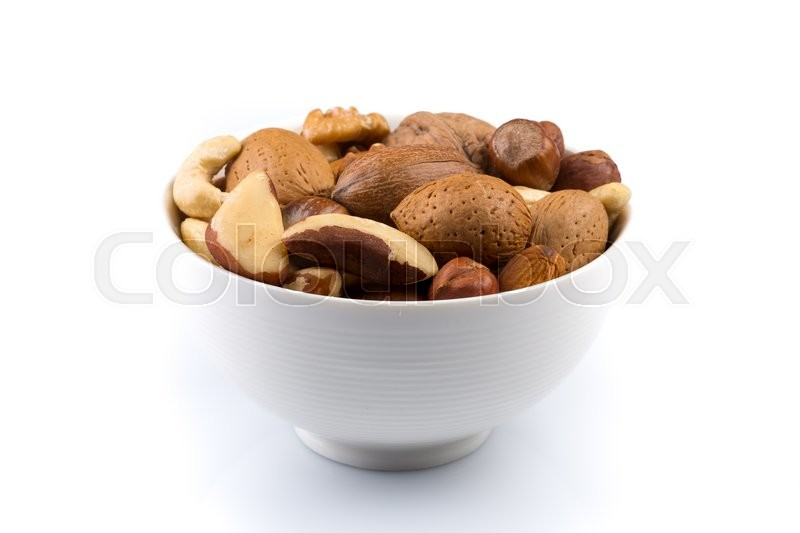 Stock image of 'Large diversity of healthy nuts in a white bowl - isolated'