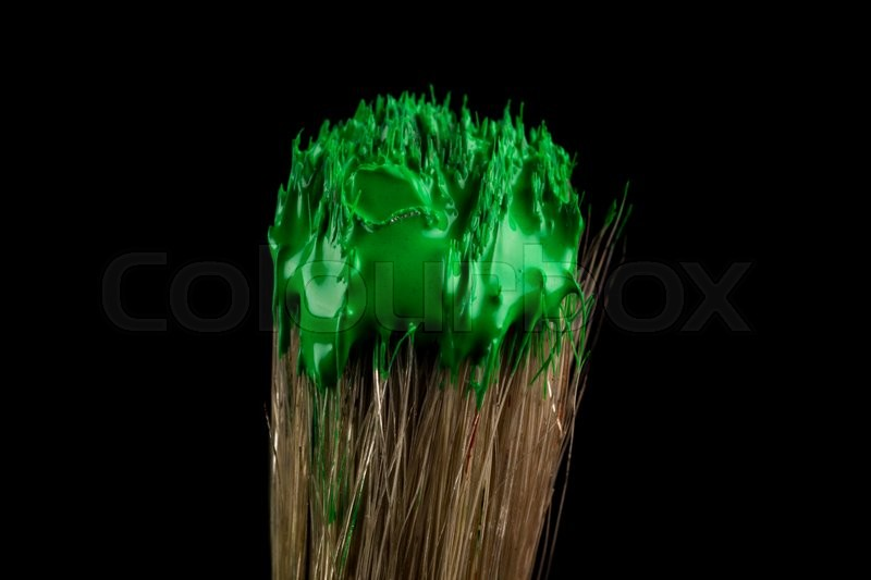 Stock image of 'paint brush painting with green color on black background'