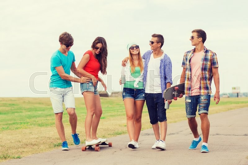 Stock image of 'holidays, vacation, love and friendship concept - group of smiling teenagers walking and riding on skateboards outdoors'