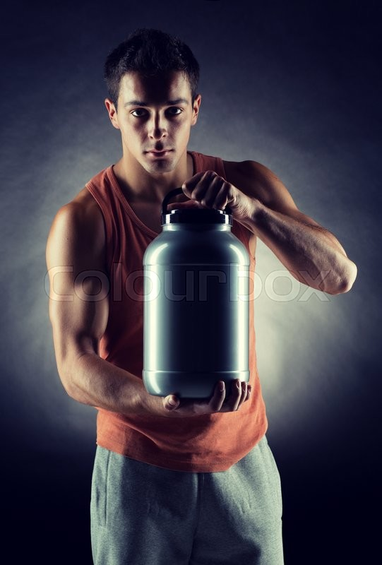 Stock image of 'sport, bodybuilding, strength and people concept - young man standing holding jar with protein over gray background'