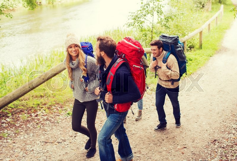 Stock image of 'adventure, travel, tourism, hike and people concept - group of smiling friends walking with backpacks'