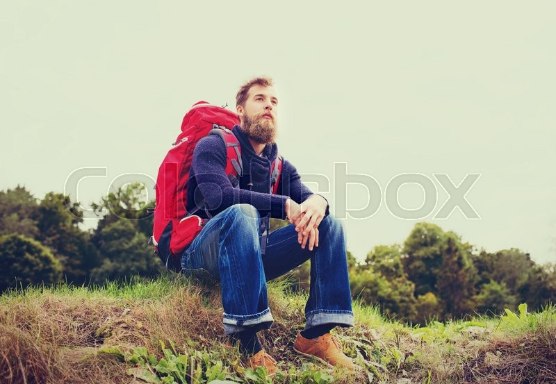 Stock image of 'adventure, travel, tourism, hike and people concept - smiling man with red backpack sitting on ground'