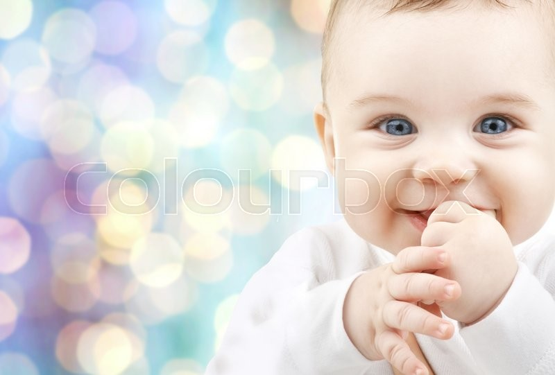 Stock image of 'children, people, infancy and age concept - beautiful happy baby boy over blue holidays lights background'