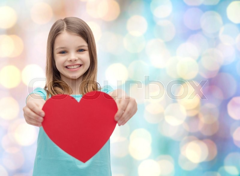 Stock image of 'love, happiness, charity, children and people concept - smiling little girl giving red heart over blue holidays lights background'