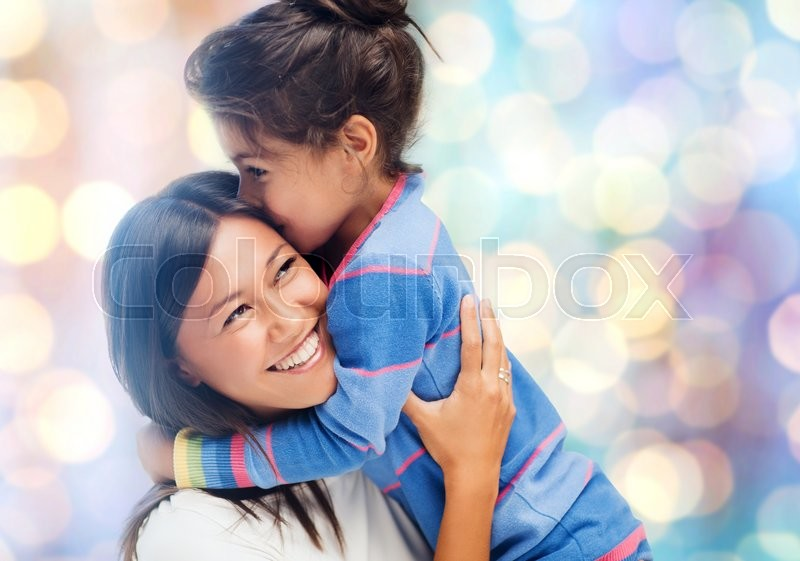 Stock image of 'people, motherhood, family and adoption concept - happy mother and daughter hugging over blue holidays lights background'