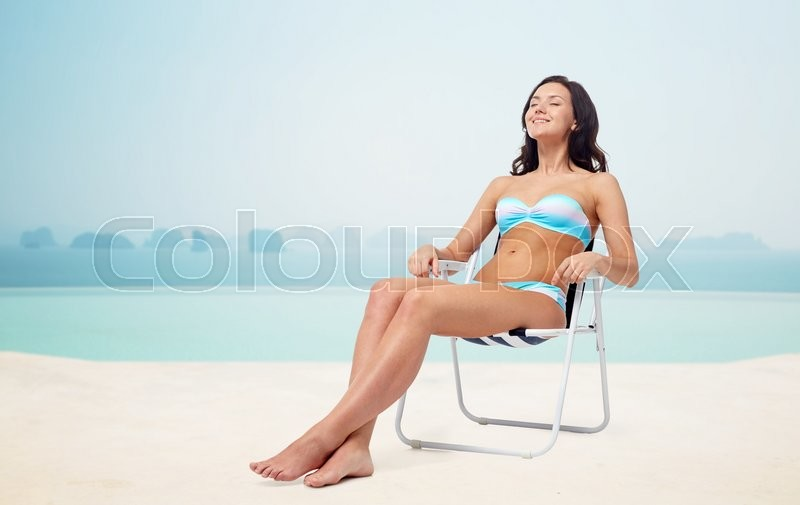Stock image of 'people, tanning, summer and beach concept - happy young woman in bikini swimsuit sunbathing on folding chair over infinity edge pool at hotel resort background'