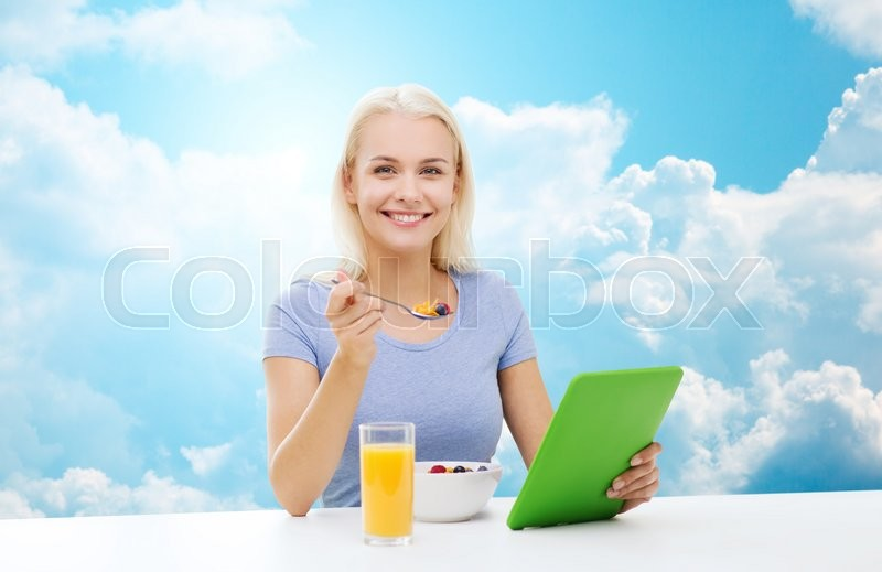 Stock image of 'healthy eating, dieting and people concept - smiling young woman with tablet pc computer eating breakfast over blue sky and clouds background'