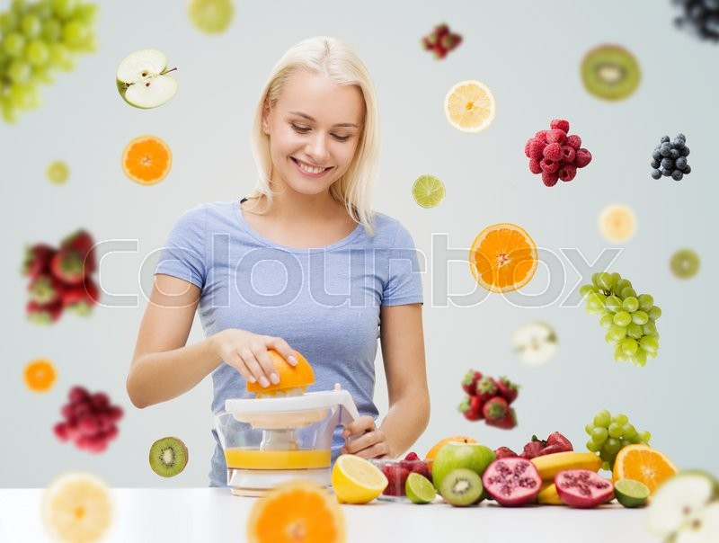 Stock image of 'healthy eating, vegetarian food, diet, detox and people concept - smiling woman with squeezer squeezing fruit juice over fruits and berries on gray background'