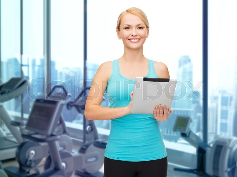 Stock image of 'sport, fitness, technology, advertisement and people concept - smiling sporty woman with tablet pc computer over gym machines background'