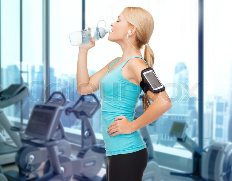 Stock image of 'sport, fitness, technology and people concept - smiling sporty woman with smartphone and earphones listening to music and drinking water over gym machines background'