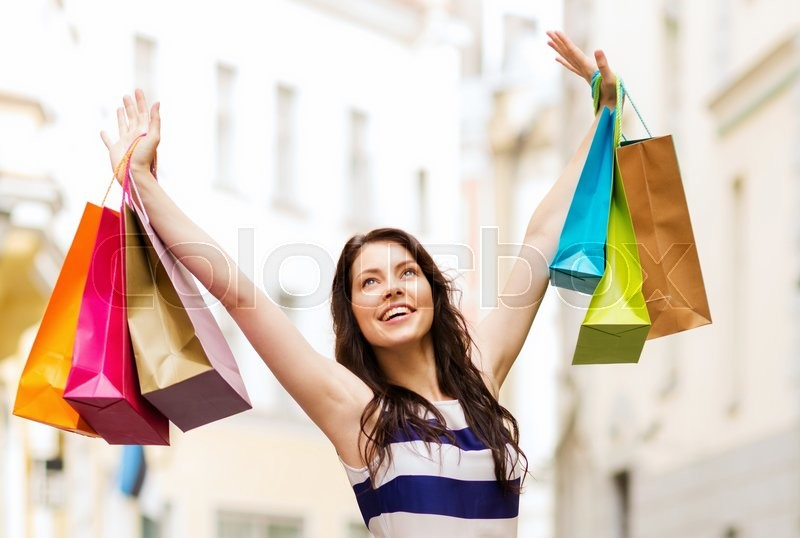 Stock image of 'shopping and tourism concept - beautiful woman with shopping bags in ctiy'