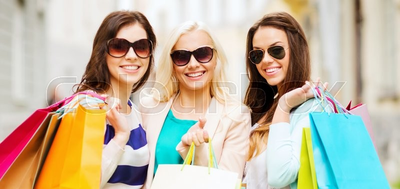 Stock image of 'shopping and tourism concept - beautiful girls with shopping bags in ctiy'