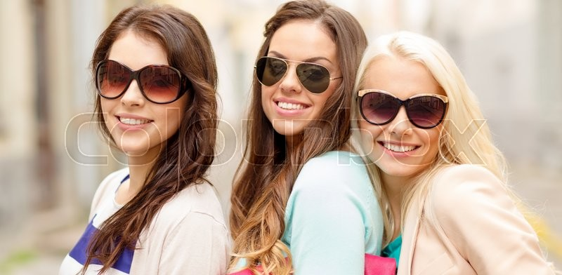 Stock image of 'holidays, tourism and happy people concept - three smiling women in sunglasses with bags in the city'