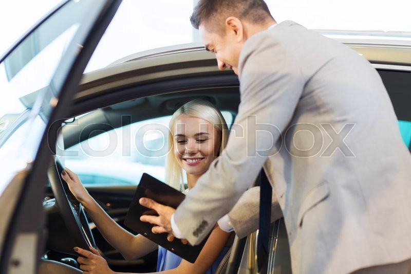 Stock image of 'auto business, car sale, consumerism and people concept - happy woman with car dealer in auto show or salon'