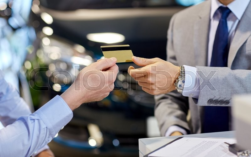 Stock image of 'auto business, sale and people concept - close up of customer giving credit card to car dealer in auto show or salon'