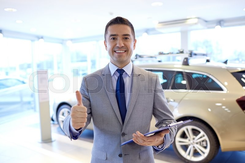 Stock image of 'auto business, car sale, consumerism, gesture and people concept - happy man with clipboard showing thumbs up at auto show or salon'