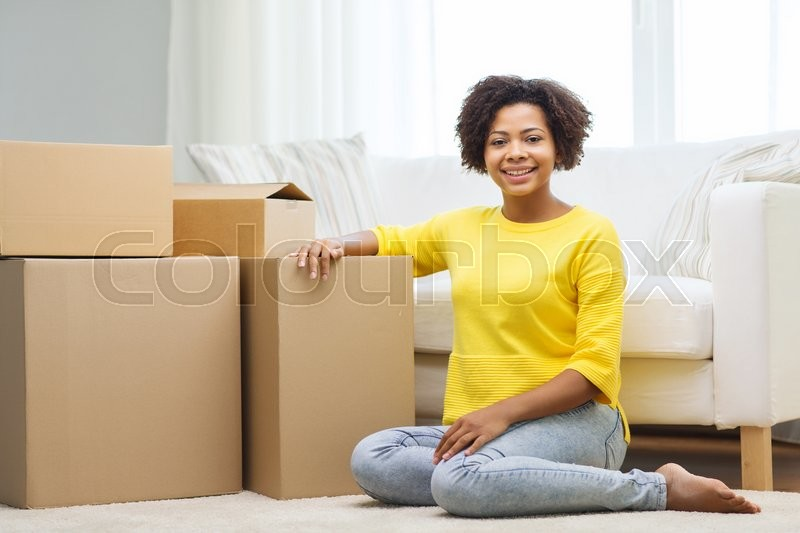 Stock image of 'people, moving new place and repair concept - happy african american young woman with many cardboard boxes sitting on floor at home'