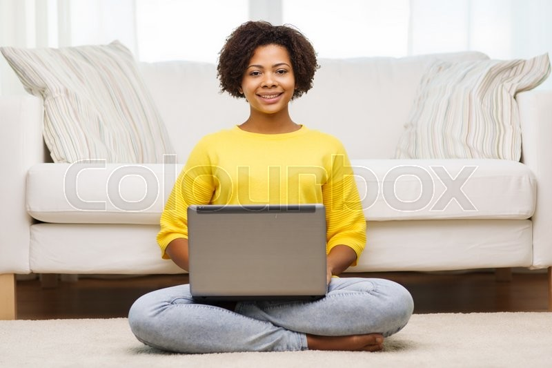 Stock image of 'people, technology and leisure concept - happy african american young woman sitting on floor with laptop computer at home'