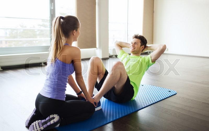 Fitness, sport, training, teamwork and people concept - woman with personal trainer doing sit ups in gym, stock photo