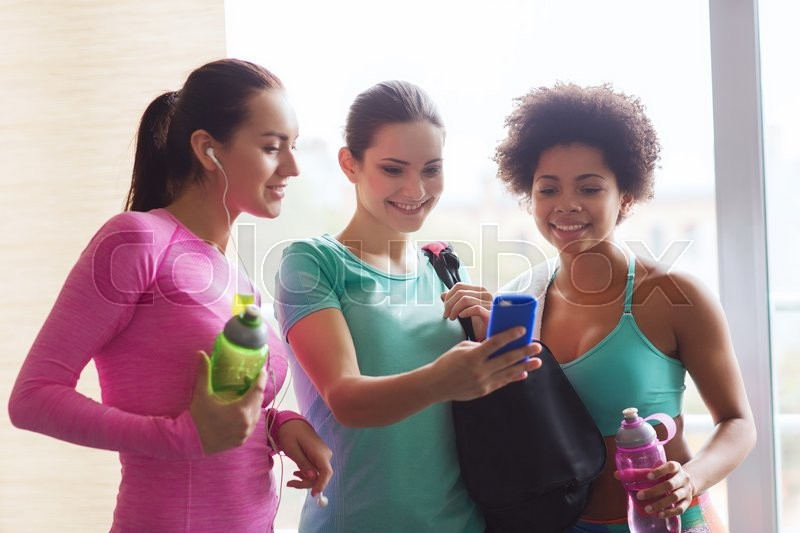 Stock image of 'fitness, sport, training, gym and lifestyle concept - group of happy women with bottles and smartphone in gym'