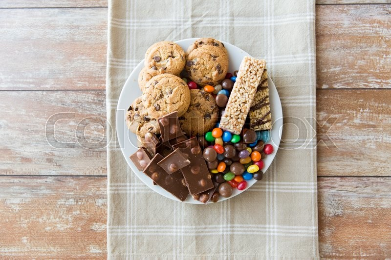 Stock image of 'junk food, sweets and unhealthy eating concept - close up of candies, chocolate, muesli and cookies on plate'
