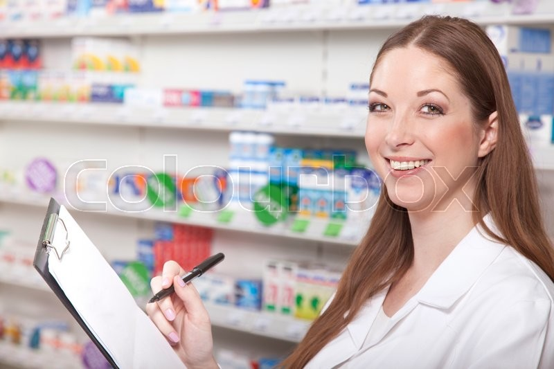 Stock image of 'Pharmacist with clipboard while stocktaking in pharmacy'