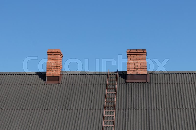 Stock image of 'A dark colored roof with two chimneys'