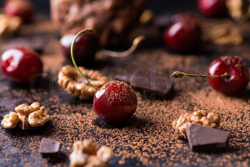 Stock image of 'Ripe cherry, cocoa powder, walnuts, and chocolate chunks on dark background, selective focus'