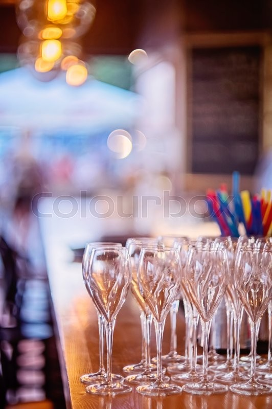 Stock image of 'Row of empty champagne glasses on the bar counter '