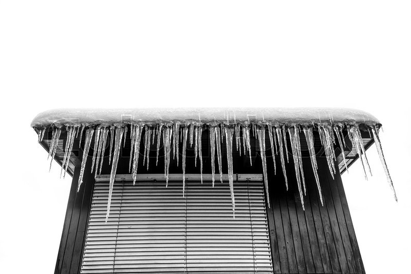 Stock image of 'Dangerous icicles hanging on a roof'
