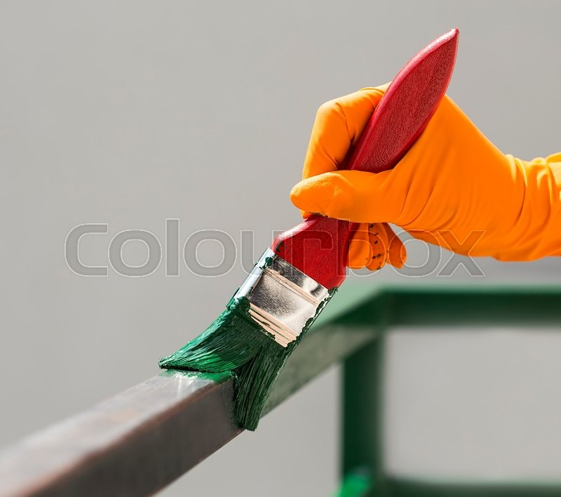 Stock image of 'Hand wearing orange gloves and painting with a paint brush.'