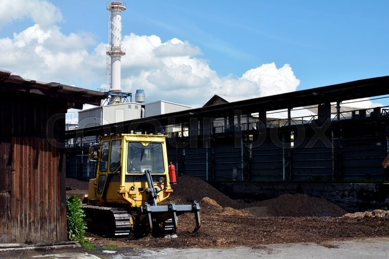 Stock image of 'A yellow bulldozer parked infront of a factory.'